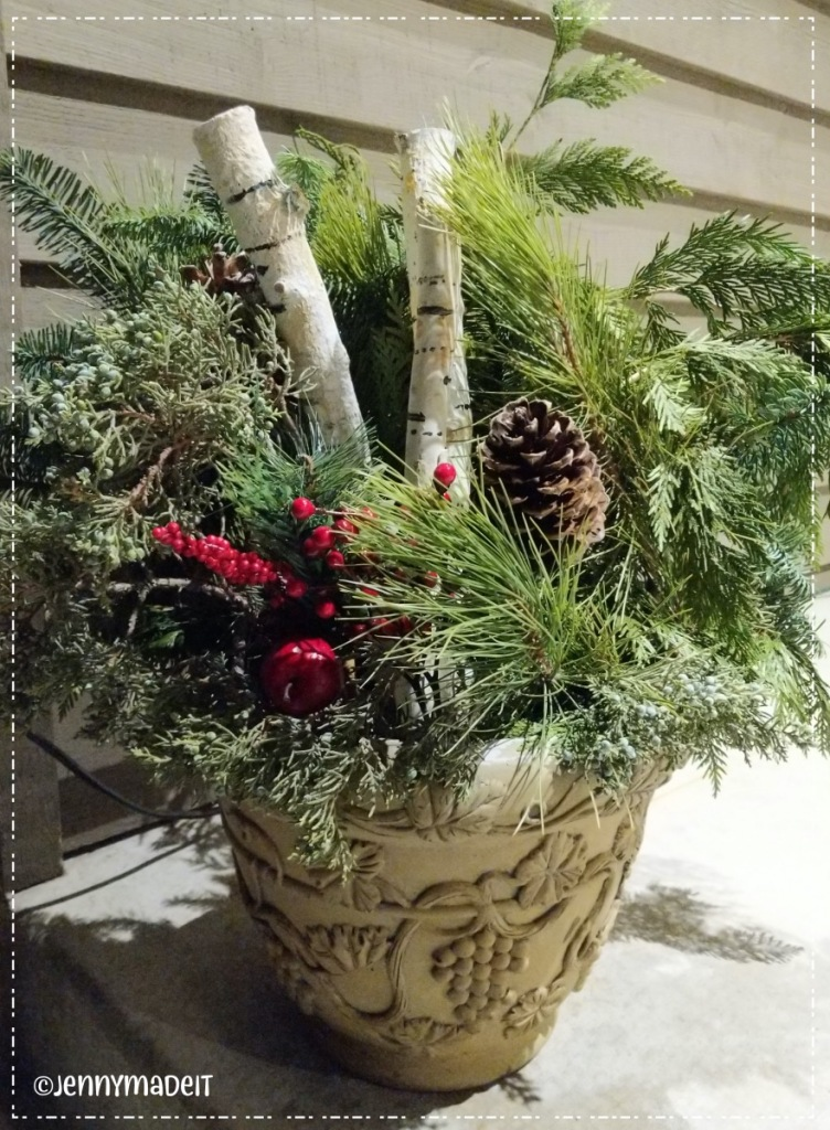 Photo of a Christmas planter with greenery, pine cones, red berries and my painted birch logs.
