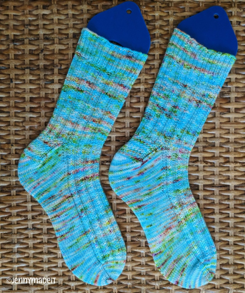 This is a photo of two knitted socks on blocking forms.
