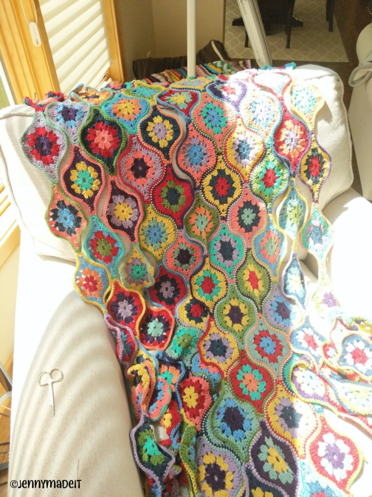 This is a photo of a crochet blanket in many bright colors that is nearly finished.