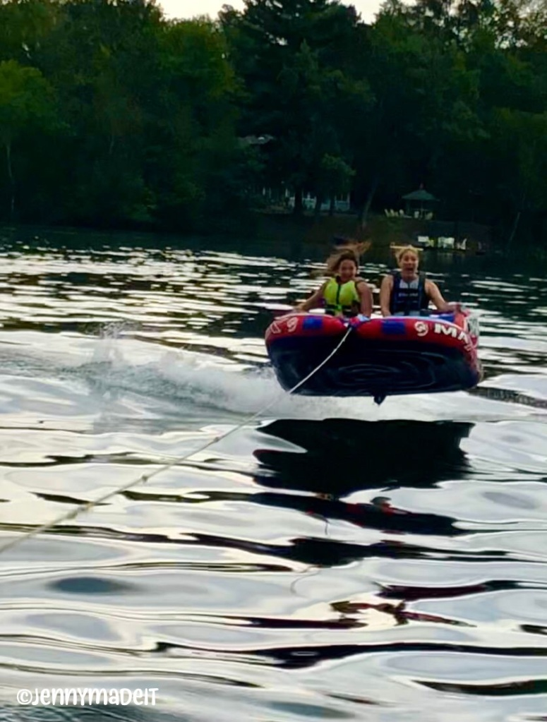 This is a photo of myself and a friend on a raft being towed by a boat on a lake. We are airborne above the water while looking frightened.